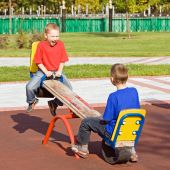 stock photo of seesaw  - Boys playing on a seesaw on a playground in a sunny day - JPG