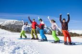stock photo of snowboarding  - One skier and 4 snowboarders standing in a row and lifting hands up in the air and making fun on the mountains background - JPG