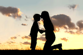stock photo of forehead  - Silhouette of a young mother lovingly kissing her little child on the forehead outside isolated in front of a sunset in the sky - JPG