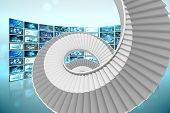 Winding stairs against screen collage showing business images
