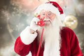 Santa claus on the phone against blurred christmas background