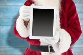 Santa claus showing tablet pc against blurred wooden planks