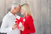 Loving couple with gift against pale grey wooden planks