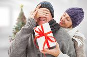 Mature woman surprising partner with gift against blurry christmas tree in room