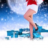 Festive womans legs in high heels against white clouds under blue sky
