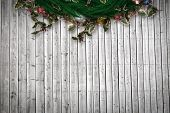 Festive christmas wreath against digitally generated grey wooden planks