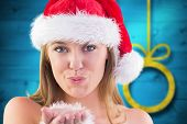 Festive blonde blowing a kiss against blurred christmas background