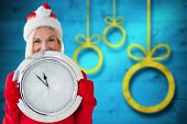 Happy festive blonde with clock against blurred christmas background
