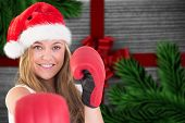 Festive blonde punching with boxing gloves against festive bow over wood