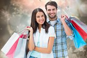Happy couple with shopping bags against blurred christmas background