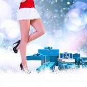 Festive womans legs in high heels against light glowing dots on blue