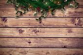 Festive christmas wreath with decorations against wooden planks background