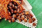 Hazelnuts in wicker basket, on napkin on wooden background