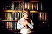 Smart boy stands in the library by the bookshelves with many old books. Educational concept. Science.