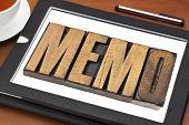 memo word in letterpress wood type on a digital tablet with tea