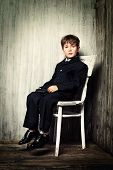 Art portrait of a boy in a suit sitting on a white chair. Educational concept.