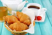 Breakfast with tea, apple juice, jam and fresh croissants on wooden table, on bright background