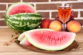 Composition of ripe watermelon, fruits, pink wine in glass and wooden barrel on  color wooden table, on bricks background