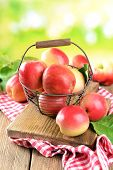 Sweet apples in wicker basket on table on bright background