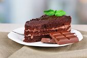 Piece of chocolate cake on plate on wooden table on natural background