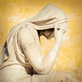 Vintage statue of a crying woman with a grunge background