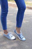 Pink sneakers on girl legs outdoors
