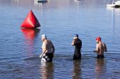 Three Swimmers Testing Water Before Swimming Race