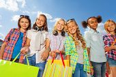 Girls with colorful shopping bags stand arm-in-arm
