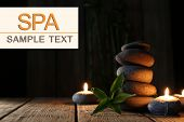Spa stones, candles on wooden table on dark background