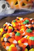 a pile of different Halloween candies with scary ornaments in the background, such as skulls, cobwebs and pumpkins