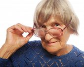 old senior lady looking through her eyeglasses isolated on white background