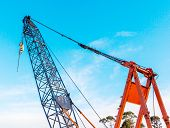 The Grunge Construction Crane For Heavy Lifting Is Working In Construction Site And Clear Blue Sky D