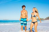 Attractive Happy Couple Walking on Sandy Beach