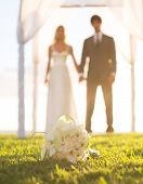 Wedding, Beautiful Bride and Groom Holding Hands. Focus of Bouquet, Shallow Depth of Field