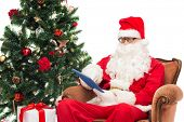 technology, holidays and people concept - man in costume of santa claus with tablet pc computer, gifts and christmas tree sitting in armchair