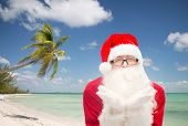 christmas, holidays, travel and people concept - man in costume of santa claus blowing on palms over tropical beach background