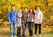 love, relationship, season, friendship and people concept - group of smiling men and women hugging in autumn park
