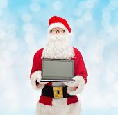 christmas, advertisement, technology, and people concept - man in costume of santa claus with laptop computer over blue lights background