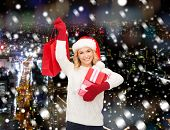 happiness, winter holidays, christmas and people concept - smiling young woman in santa helper hat with gifts and shopping bag over snowy night city background