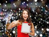christmas, technology, present and people concept - smiling woman in red dress with blank tablet pc computer screen over snowy night city background