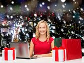 christmas, holidays, technology, advertising and people concept - smiling woman in red blank shirt with shopping bags and laptop computer over snowy city background
