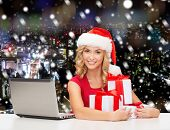 christmas, holidays, technology and people concept - smiling woman in santa helper hat with gifts and laptop computer over snowy city background