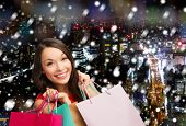 happiness, winter holidays, christmas and people concept - smiling young woman with shopping bags over snowy night city background