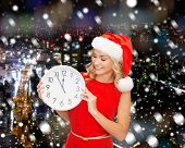 christmas, winter, holidays, time and people concept - smiling woman in santa helper hat and red dress with clock over snowy night city background