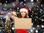 christmas, winter, holidays, delivery and people concept - smiling woman in santa helper hat with parcel box over snowy night city background