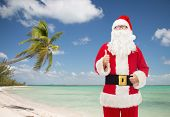 christmas, holidays, gesture, travel and people concept- man in costume of santa claus showing thumbs up over tropical beach background