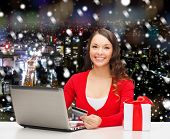 christmas, holidays, technology and shopping concept - smiling woman with credit card, gift box and laptop computer over snowy night city background