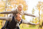 love, relationship, family and people concept - smiling couple having fun in autumn park