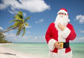 christmas, holidays, travel and people concept - man in costume of santa claus over tropical beach background