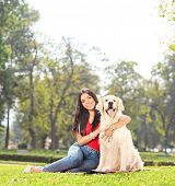 Young girl posing with her dog in a park shot with a tilt and shift lens